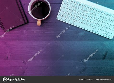 Computer keyboard with coffee and notebook on office desk